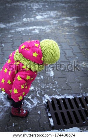 Curious baby looks on sump - stock photo