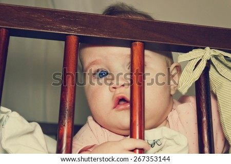 curious baby peeping out of his crib. carefree childhood. toned image - stock photo