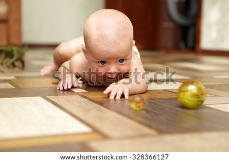 Curious baby playing with ball on a floor