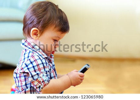 curious baby toddler exploring mobile phone - stock photo