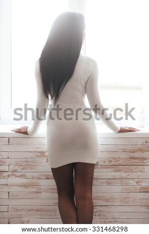 Curious beauty. Rear view of beautiful young African woman in sweater looking through a window while leaning at the window sill