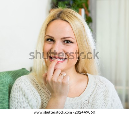 Curious  blonde housewife sitting on sofa at domestic interior