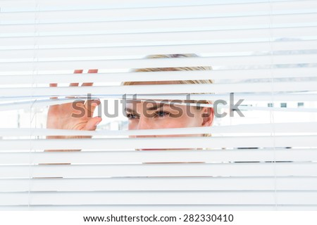 Curious blonde woman looking through venetian blind on a sunny day - stock photo