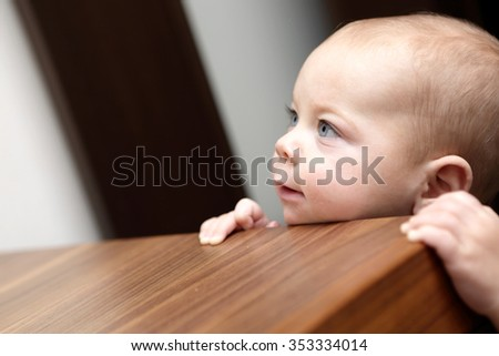 Curious boy and a chest of drawers at home - stock photo