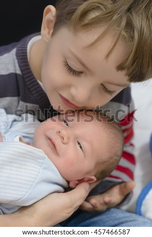 Curious Boy holding his little brother, black background