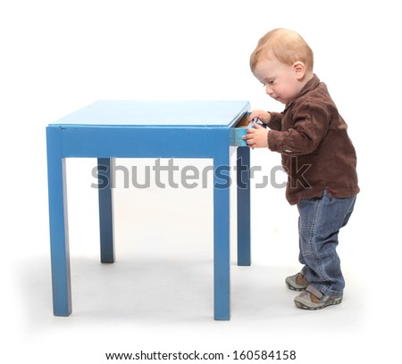 Curious boy peeks into drawer to see what is inside.  - stock photo