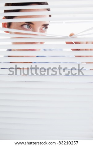 Curious brunette Woman peeking out of a window in an office