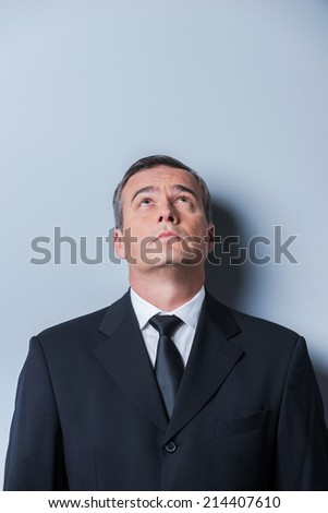 Curious businessman. Curious mature man in formalwear looking up while standing against grey background - stock photo