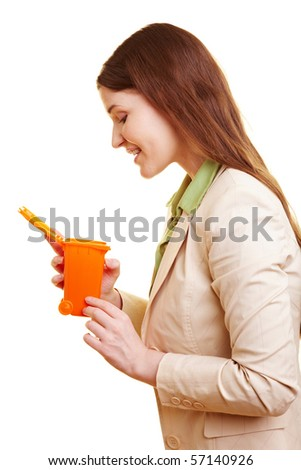 Curious businesswoman looking into a small garbage can - stock photo
