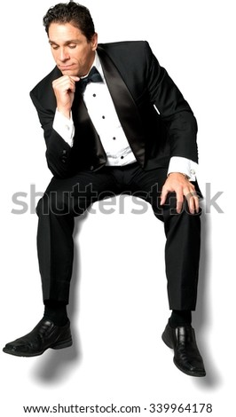 Curious Caucasian man with short black hair in a tuxedo sitting and thinking - Isolated - stock photo