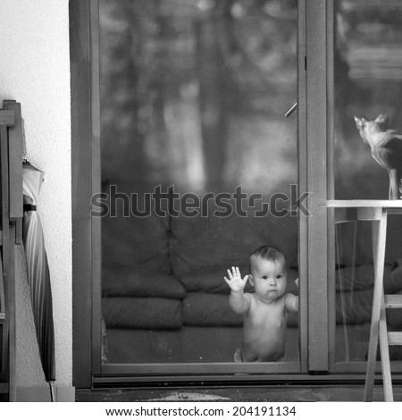 Curious child kneeling behind the glass doors looking outdoors  - stock photo