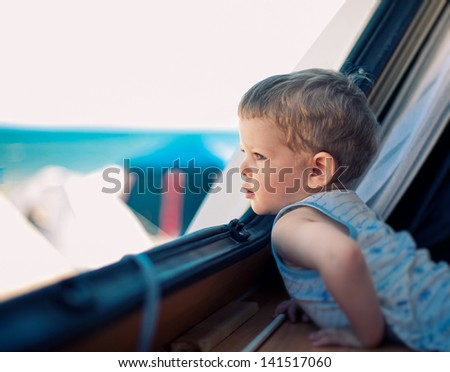 curious child looking out of the window on the sea beach - stock photo
