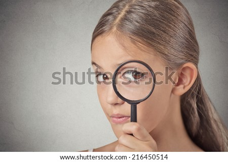 Curious. Child looking through a magnifying glass, isolated on grey wall background. Human face expressions - stock photo