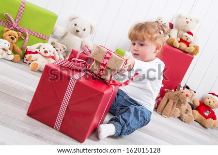 Curious child: young girl opening Christmas present with teddy bears in background - stock photo