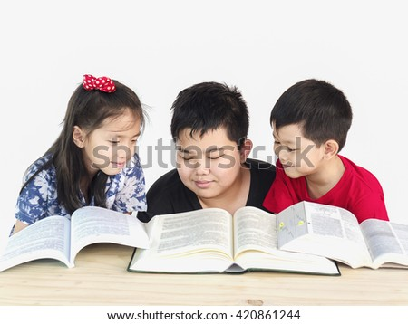 Curious children reading book together - stock photo