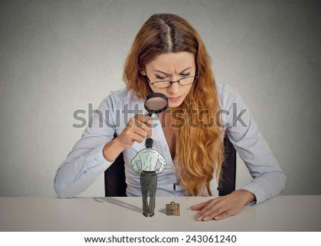 Curious corporate businesswoman skeptically meeting looking at small employee standing on table through magnifying glass isolated grey office wall background. Human face expression attitude perception - stock photo