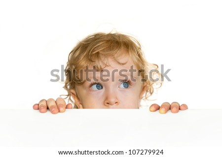 Curious cute child looking over the table edge - stock photo