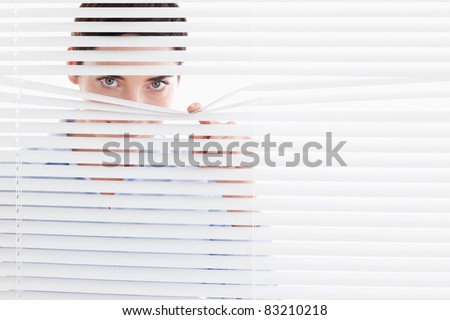 Curious cute Woman peeking out of a window in an office