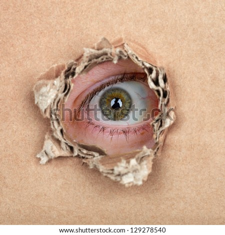 Curious espionage eye in hole in brown carton wall - stock photo