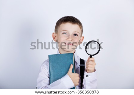 Curious Exploring little boy with magnifying glass holding a book on white background. - stock photo