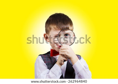 Curious Exploring little boy with magnifying glass, on yellow background. - stock photo