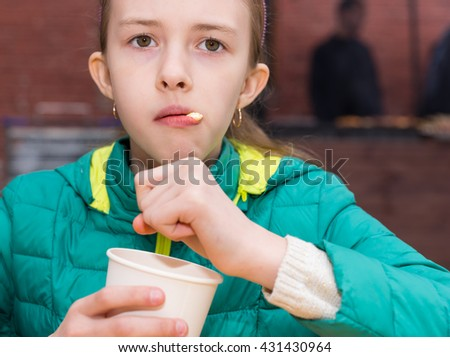 Curious female child in green winter coat staring ahead while eating ice cream or other dessert as tongue licks food from lips - stock photo