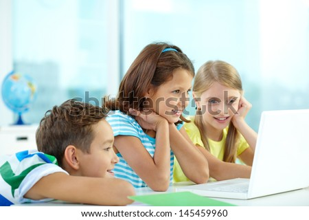 Curious friends watching some interesting stuff on the laptop - stock photo
