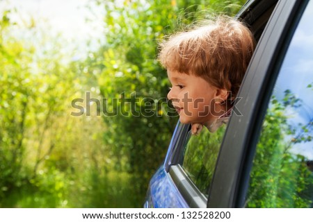 curious funny little kid looking outside of car window - stock photo