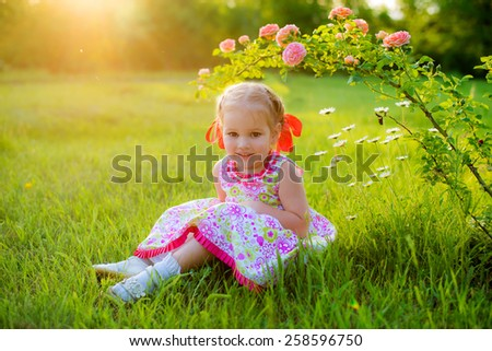 curious girl in beautiful summer dress with a red bow on her head in the spring park sitting on the grass under a bush - stock photo