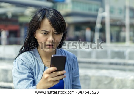 Curious girl looking at her mobile smart-phone