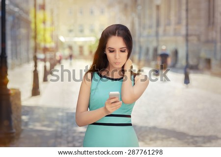 Curious Girl Looking at Her Phone - Portrait of a urban young woman checking out her phone   - stock photo