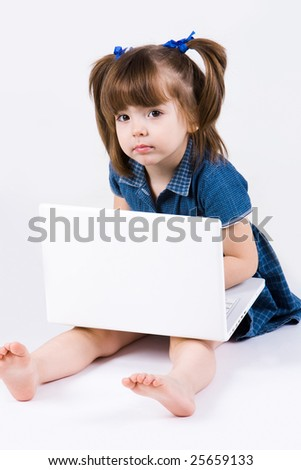 Curious girl sitting with laptop on her knees and looking at camera - stock photo