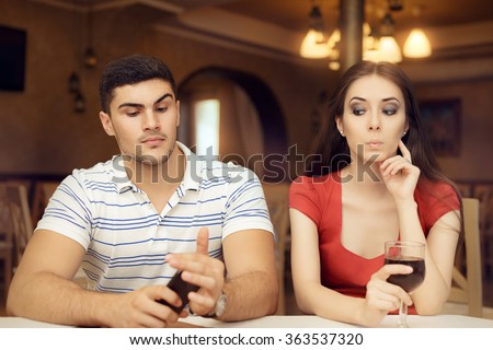 Curious Girl Spying Boyfriend on Smartphone - Secretive couple having a bad date in a restaurant  - stock photo