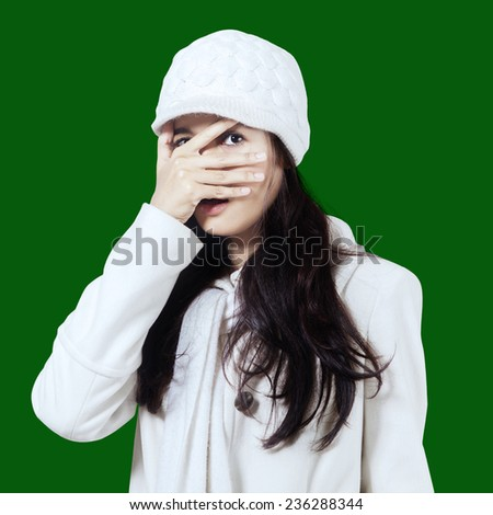 Curious girl wearing winter coat and hat, peeping at the camera through her fingers in the studio - stock photo