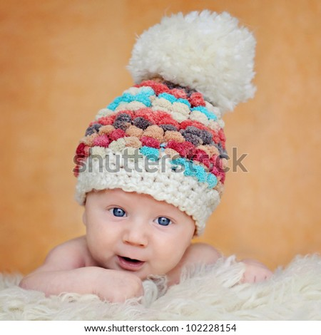 Curious, happy, two months old baby in cute hat - stock photo