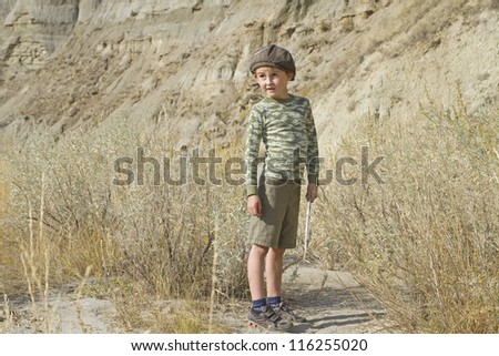 Curious happy young boy hikes in the bad lands in Dinosaur Provincial Park - stock photo