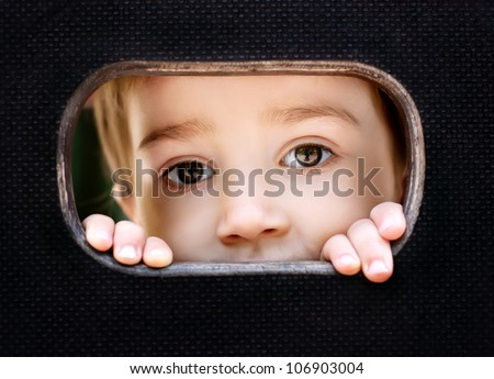Curious kid spying through the hole in the wooden wall on playground - stock photo