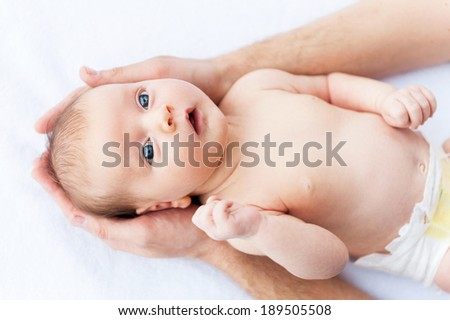 Curious little baby. Top view of male hands holding cute little baby