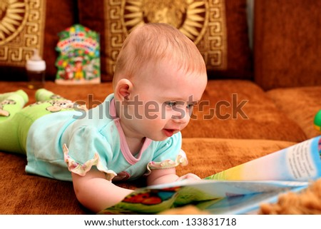 Curious Little Baby with a Book on the Sofa - stock photo