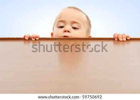 Curious little boy climbing up and looking onto table surface - stock photo