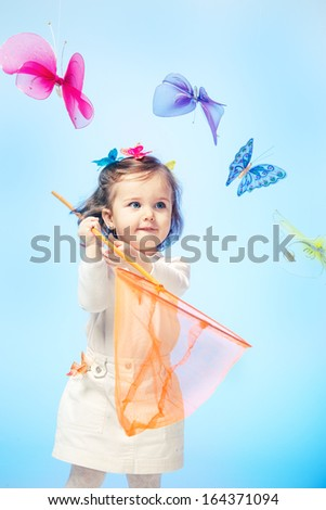Curious little girl holding butterfly net in hands - stock photo