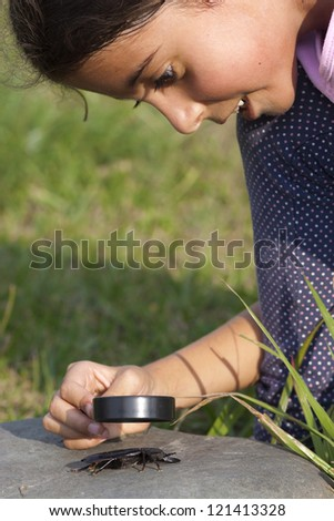 Curious Little Girl Looking At Beetle Through Magnifying Glass Outdoor - stock photo