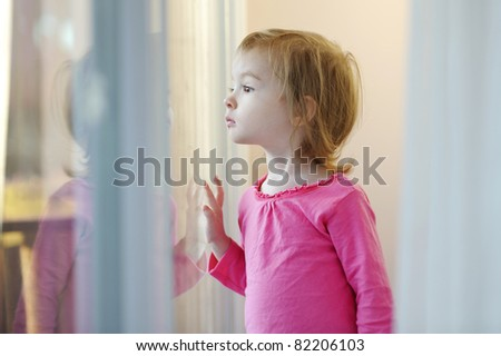 Curious little girl looking out of the window - stock photo