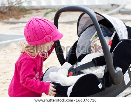 curious little girl looks in a car seat where sleeping brother - stock photo
