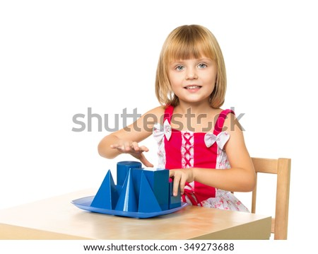 Curious little girl sitting at a table in a Montessori kindergarten . girl exploring geometric shapes - Isolated on white background - stock photo
