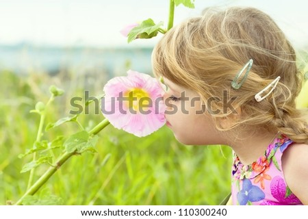 Curious little girl smells a flower - stock photo