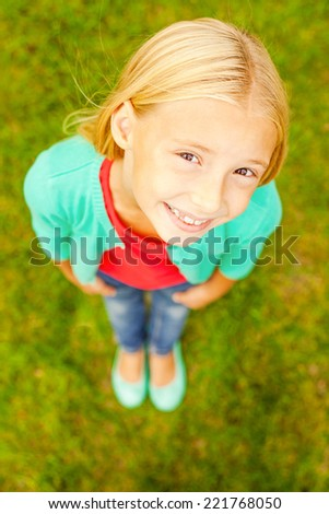 Curious little girl. Top view of cute little girl looking at camera and smiling while standing outdoors - stock photo