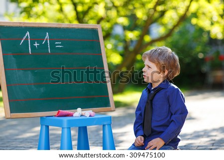 Curious little preschool boy at blackboard practicing mathematics, outdoors. Back to school concept. Lifestyle, kids, education. - stock photo