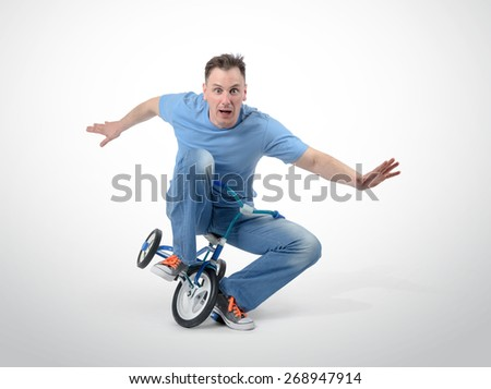 Curious man on a children's bicycle on white background - stock photo