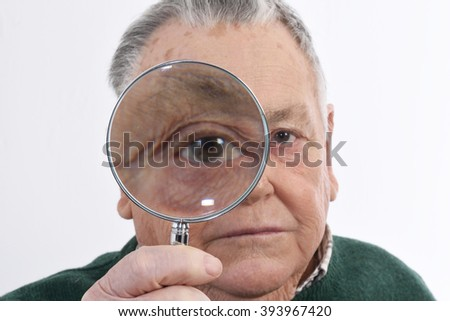 Curious man peering through magnifying glass - stock photo